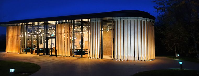 Image of a futuristic building lit up at night with wooden solar shading system