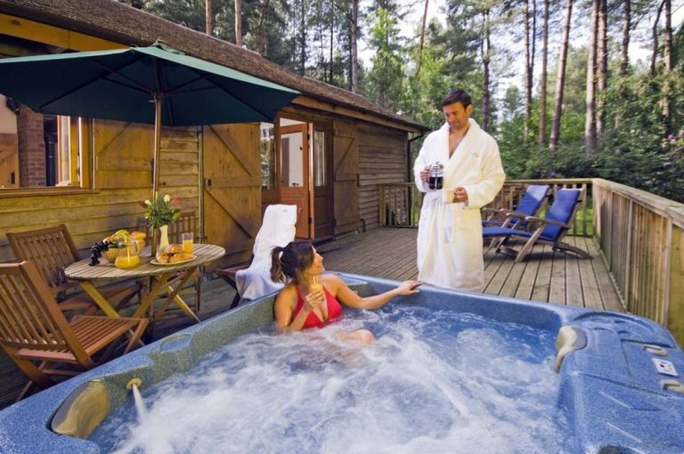 Image of a couple in a hot tub outside of a log cabin