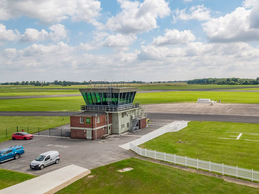 Image of an air traffic control building with a runway in the background